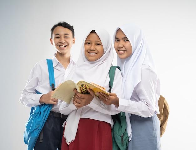 Três adolescentes vestindo uniformes escolares sorriem para a câmera com uma mochila e um livro