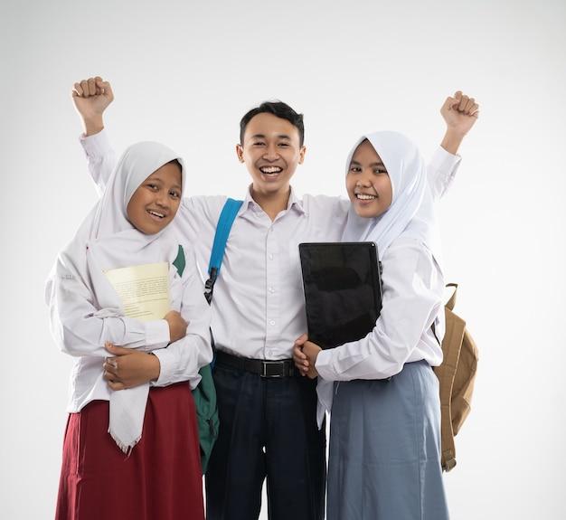 Três adolescentes vestindo uniformes escolares sorriem para a câmera com uma mochila, um livro e um comp ...