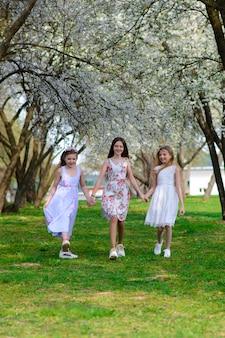 Três adoráveis garotas em vestidos de mãos dadas no jardim, parque.