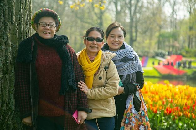 Três adulto sênior asiático sorrindo para a câmera em keukenhof, holanda.