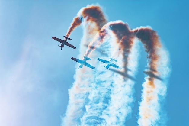 Três aeronaves de motores leves realizam acrobacias - um beco sem saída. o sol brilhante ilumina os aviões e as sombras caem na fumaça que eles deixam no céu.