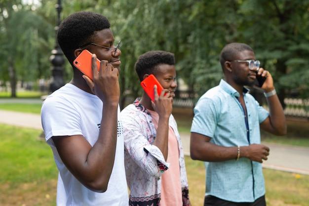 Três africanos falando ao celular