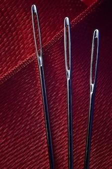 Três agulhas de costura em um fundo de tecido vermelho. fechar-se.
