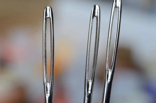Três agulhas de costura no fundo de muitos babinets multicoloridos. olho de agulha. macro.
