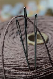 Três agulhas de costura são inseridas em um carretel de linha. fechar-se.