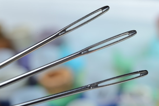 Três agulhas de costura sobre muitos babinets multicoloridos. olho de agulha. macro.
