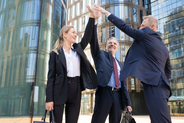 Três alegres empresários dando cinco e sorrindo. colegas confiantes e felizes celebrando um acordo de sucesso juntos, em pé ao ar livre e levantando a mão. conceito de trabalho em equipe e parceria
