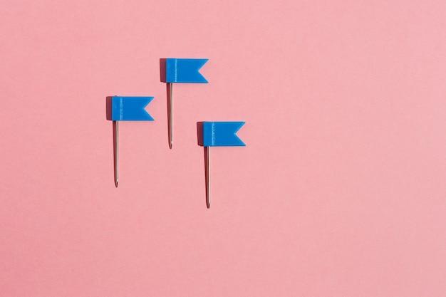 Três alfinetes de bandeira azul em um fundo rosa. vista de cima .