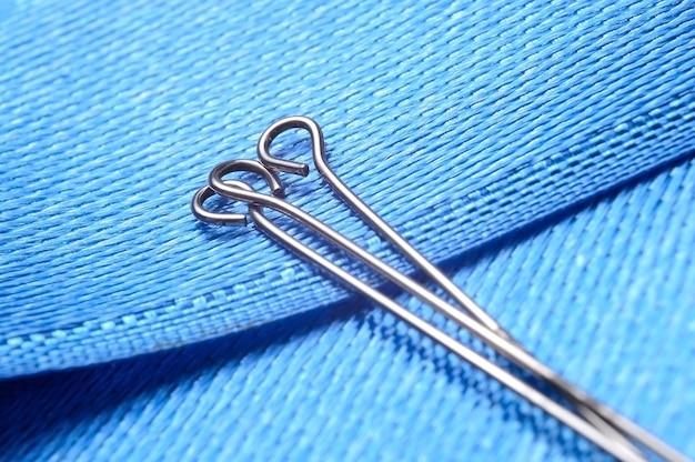 Três alfinetes de costura em um fundo de tecido azul. fechar-se.