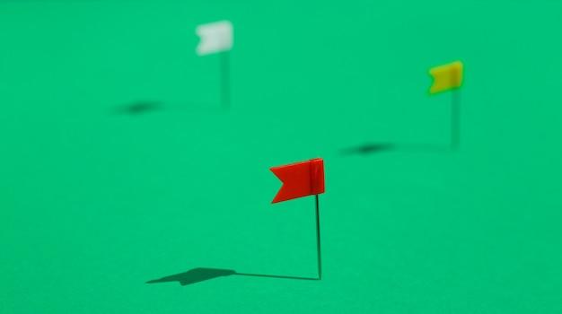 Três alfinetes de pequena bandeira coloridos fixados em uma superfície verde. conceito de negócios ou viagens. os objetivos .