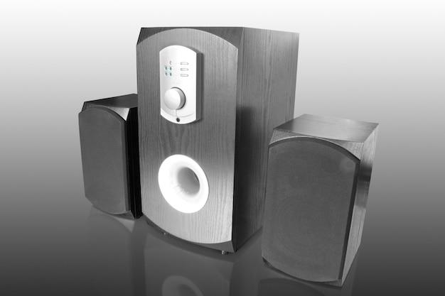 Três alto-falantes pretos com amplificador integrado, isolados no branco com reflexo