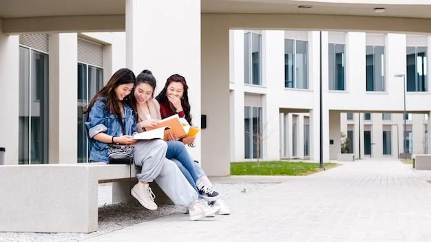 Três alunas asiáticas conversando no intervalo, sentadas no campus