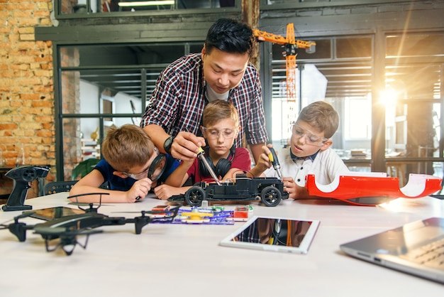 Três alunos caucasianos com professor de física reparam o modelo de carro de brinquedo controlado por rádio.