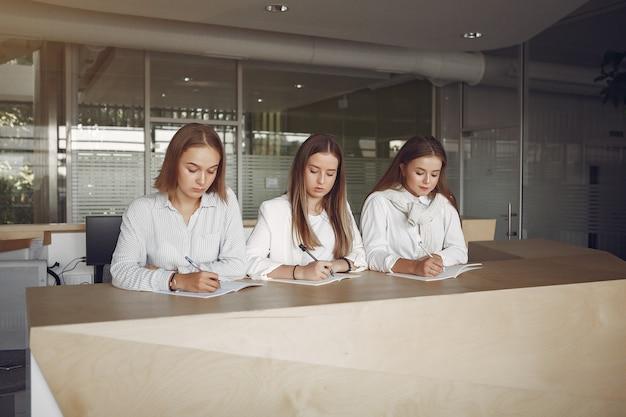Três alunos sentados à mesa na sala de aula