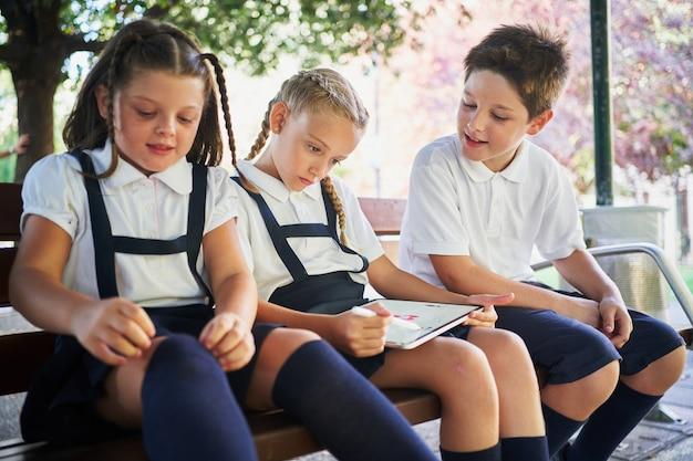 Três alunos sentados em um banco desenhando no tablet