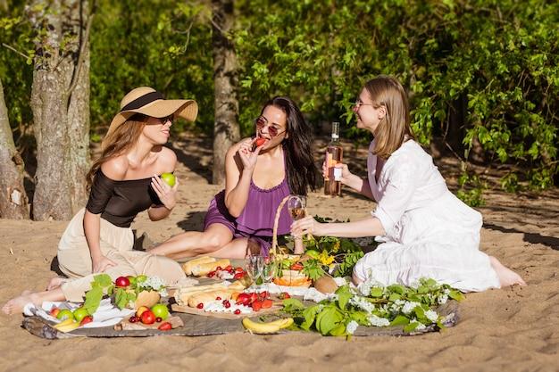 Três amigas alegres em um piquenique de verão mulheres felizes bebem vinho nas férias de natureza da garota livre ...