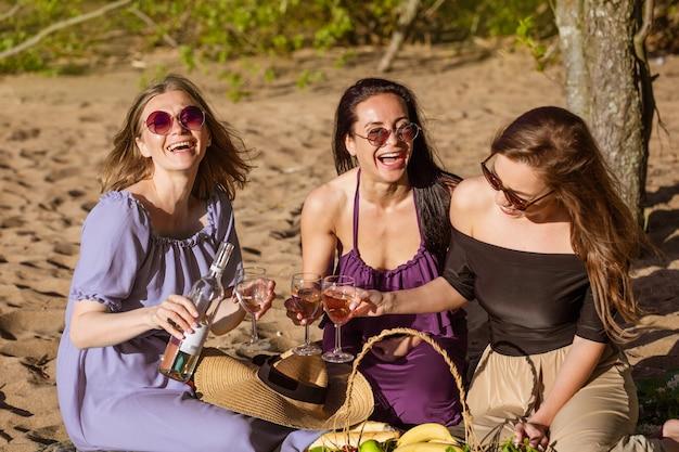 Três amigas alegres em um piquenique de verão