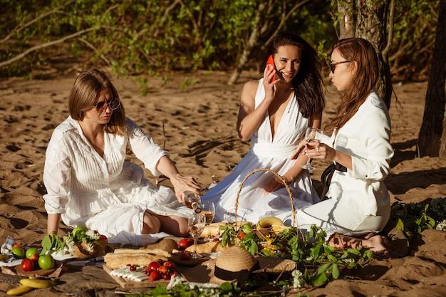 Três amigas alegres em um piquenique no verão na praia bebem vinho