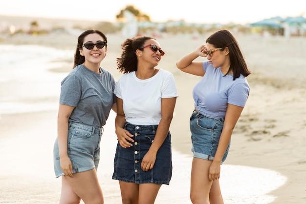 Três amigas com óculos de sol na praia