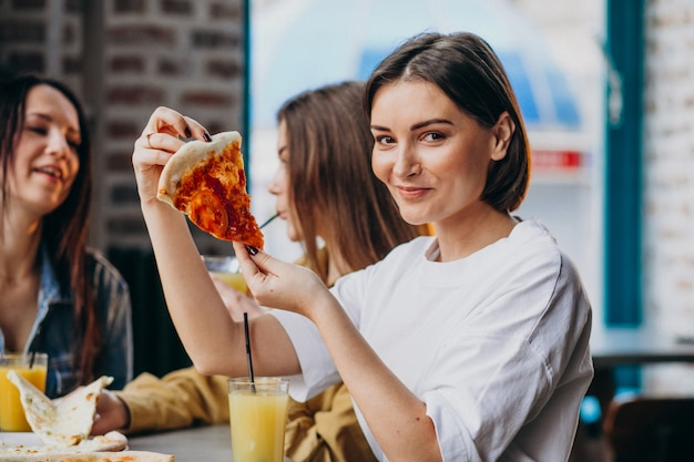 Três amigas comendo pizza em um bar
