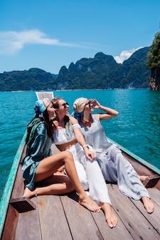 Três amigas de turistas viajam pelo parque nacional khao sok, de férias na tailândia. vela em barco asiático no lago em dia ensolarado, com vista deslumbrante.