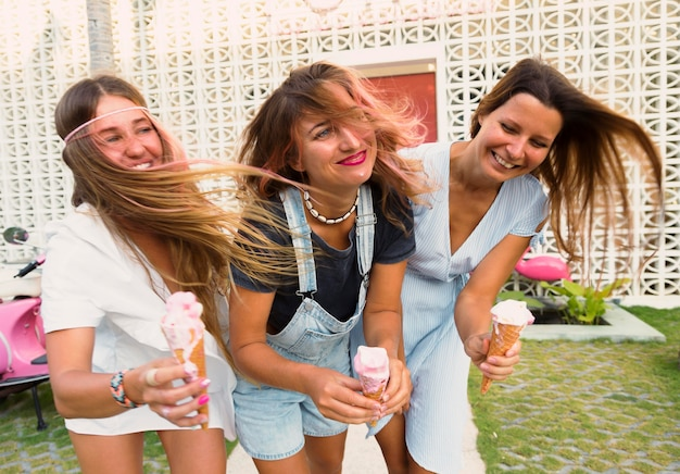 Três amigas felizes tomando sorvete