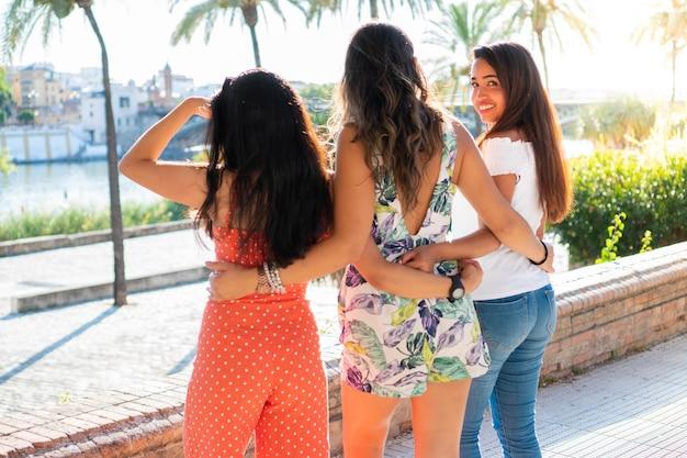 Três amigas latinas em um dia ensolarado garota olhando para a câmera jovens amigas com roupas de verão