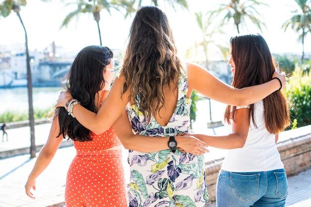 Três amigas latinas em um dia ensolarado. jovens mulheres morenas hispânicas se abraçando