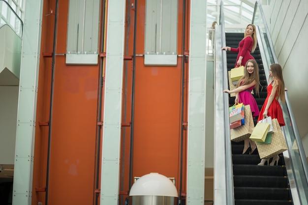 Três amigas na escada rolante com sacolas de compras