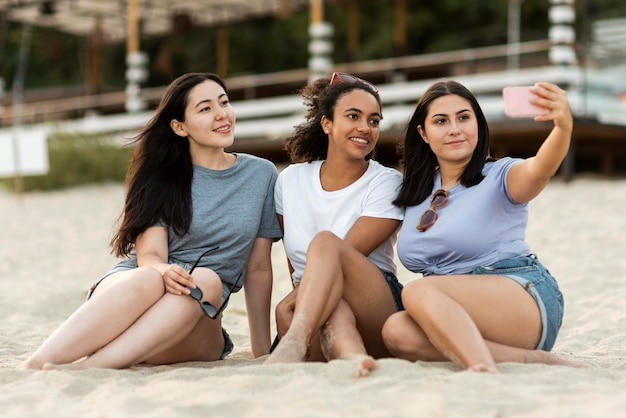 Três amigas sentadas na praia tirando uma selfie
