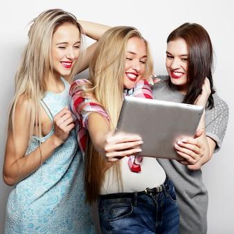 Três amigas tomando selfie com tablet digital