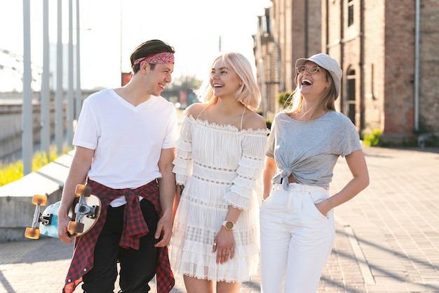 Três amigos adolescentes felizes caminhando por uma cidade