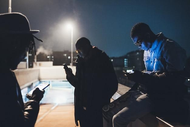 Três amigos africanos sentado ao ar livre e olhando o smartphone
