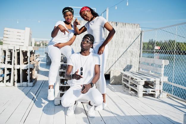 Três amigos afro-americanos elegantes, vestem-se com roupas brancas no cais na praia. moda de rua dos jovens negros. homem negro com duas garotas africanas.