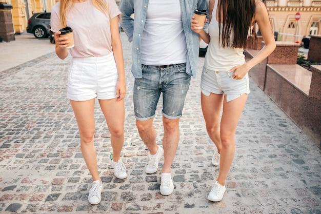 Três amigos andando na rua