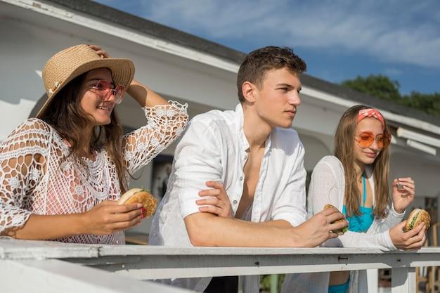 Três amigos ao ar livre comendo hambúrgueres juntos