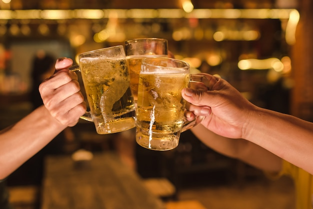 Três amigos brindando com copos de cerveja light no pub