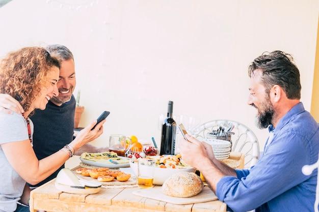 Três amigos caucasianos comendo no restaurante cada um olhando para o telefone e não falando com os outros