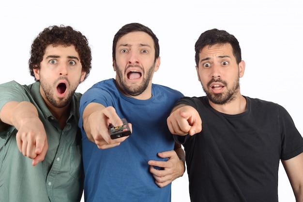 Três amigos chocados assistindo a um filme.
