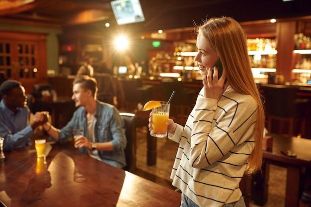 Três amigos com bebidas alcoólicas se divertindo na mesa do bar. grupo de pessoas relaxando no bar, estilo de vida noturno, amizade, celebração de evento