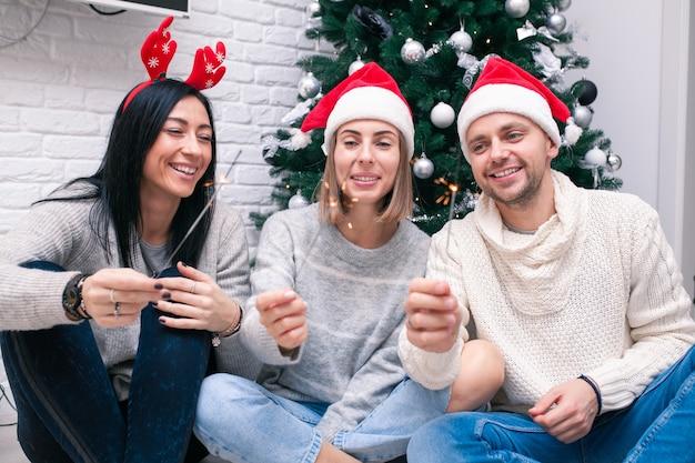 Três amigos com brilho sentados perto da árvore de natal