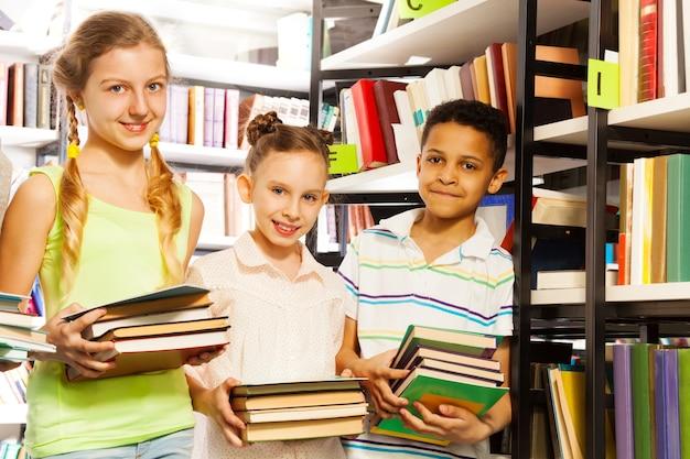 Três amigos com livros perto de uma estante na biblioteca