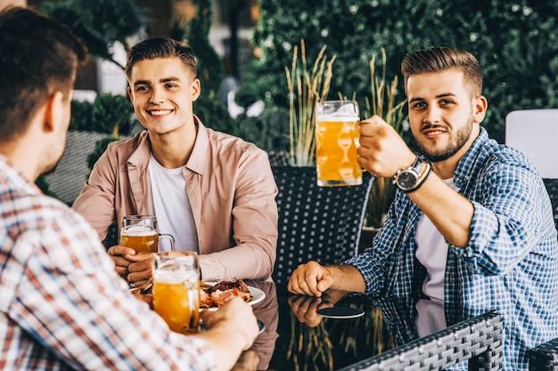 Três amigos comendo em um café e bebendo cerveja
