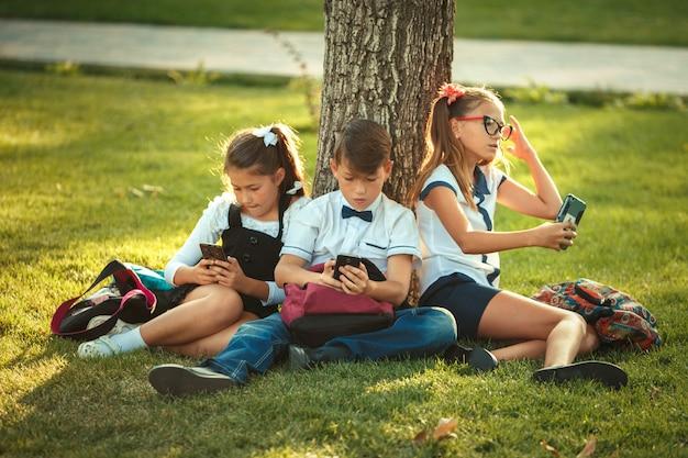 Três amigos da escola estão sentados na grama debaixo de uma árvore e tocando seus gadgets. amigos não se comunicam na vida, preferindo o telefone