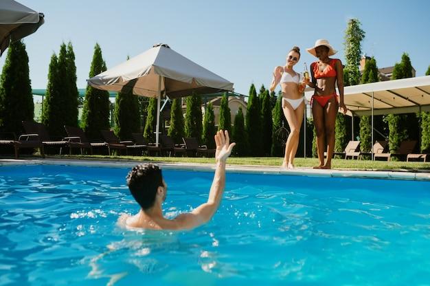 Três amigos de lazer na piscina do hotel