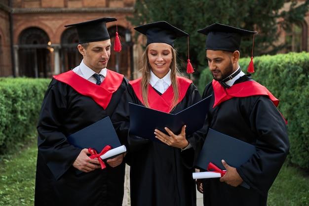 Três amigos de pós-graduação em vestes de formatura, olhando para seu diploma no campus.