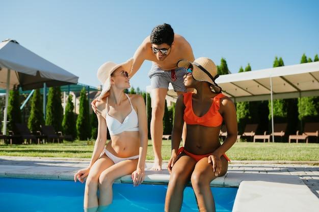Três amigos descansam na beira da piscina