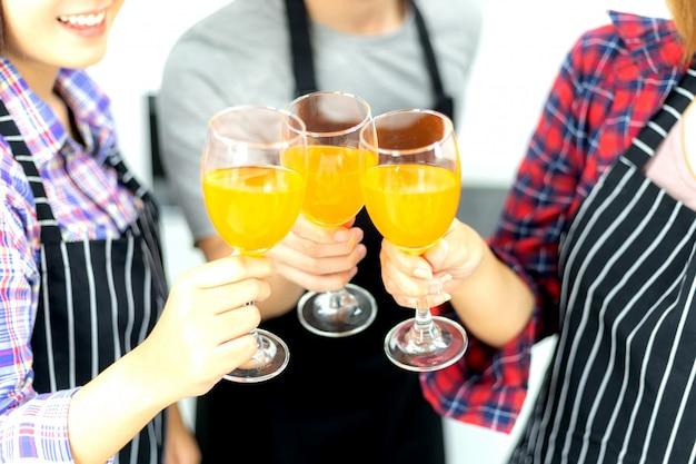 Três amigos, desfrutando, copo partido, bebendo, suco laranja, coquetel, junto