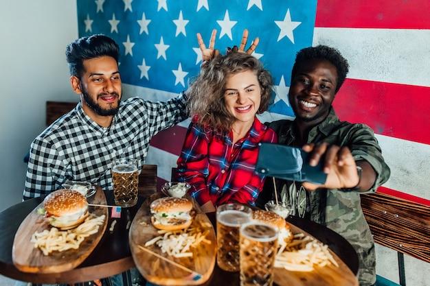 Três amigos em um restaurante de fast food tirando uma selfie enquanto comem hambúrgueres e bebem cerveja