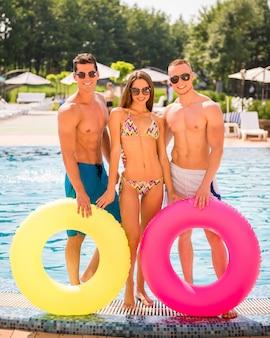 Três amigos está posando na piscina com anéis de borracha.